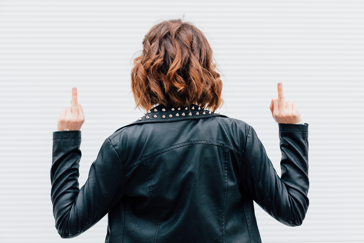 Hipster woman show middle finger, fuck you off sign in front of a white wall. Outdoor funny lifestyle portrait, concept of brutal, punk, furious, indecent.