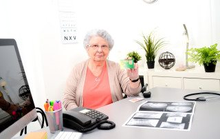 Senior woman in doctor's office showing carte vitale medical french social security card