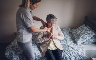The woman is helping a senior woman dress in her bedroom.